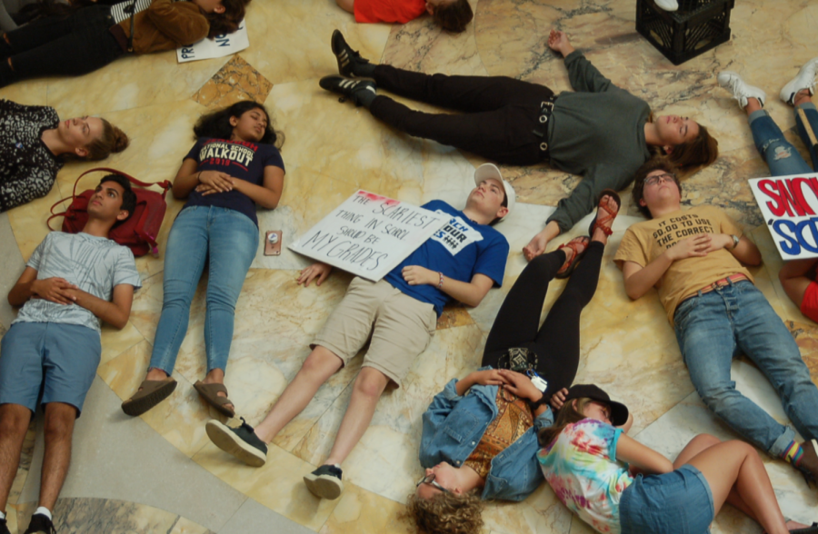 Students mimic being dead by laying on the floor