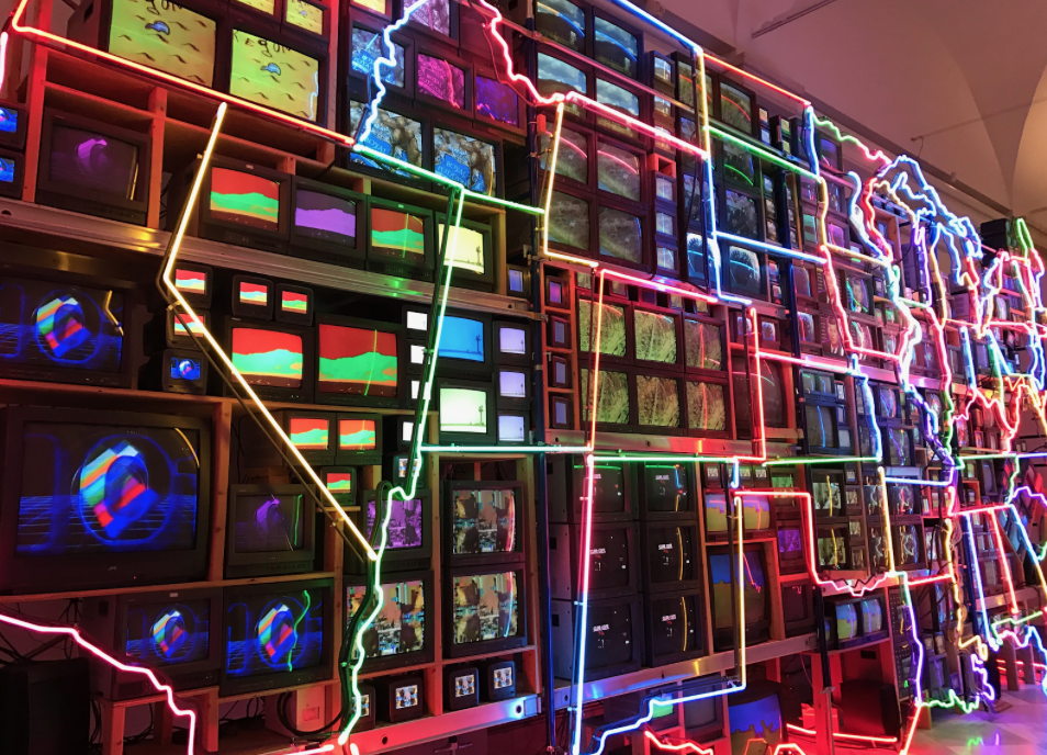 Various-sized televisions, outlined by neon lighting, create the configuration of the United States.