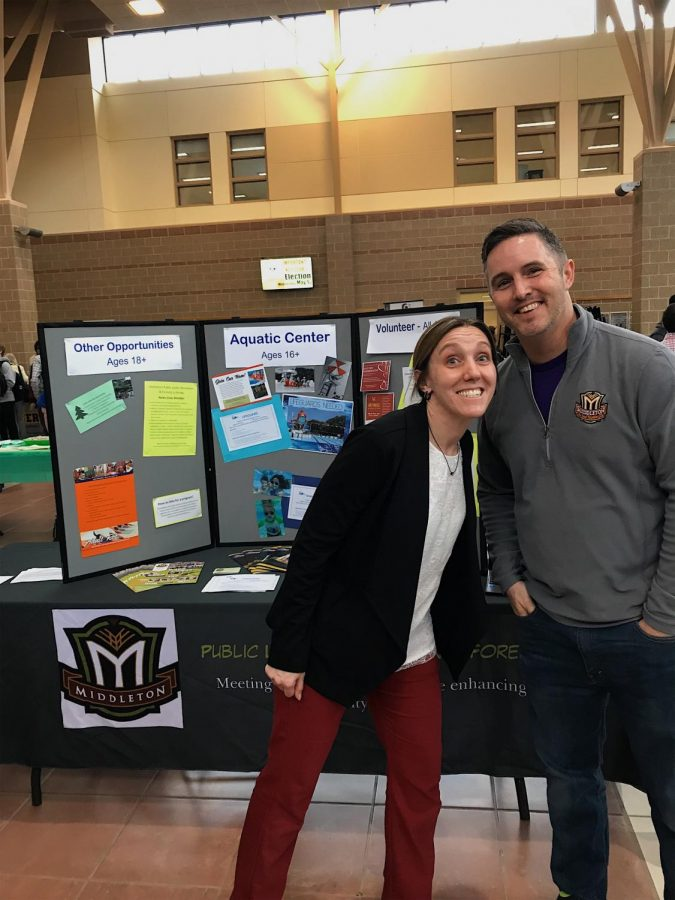 Rebecca Price (left), the Recreation Director for the Middleton Public Lands, Recreation (Middleton PLRF), and Forestry Department, and Greg Lamping (right), the Recreation Coordinator for the Middleton PLRF, stand in front of their booth at the MHS Job Fair.