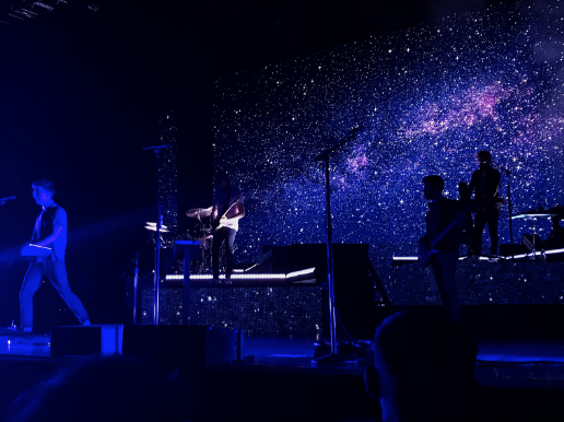 To set the mood for a song, AJR briefly performs with screen behind them that displays an image of space.