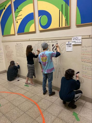 """Ohly and her creative writing students working together to create the """"BeyONd our Walls"""" exhibit in the four corners staircase of MHS. Student writers combine poetry and design to display their works relating to the theme of """"walls."""""""